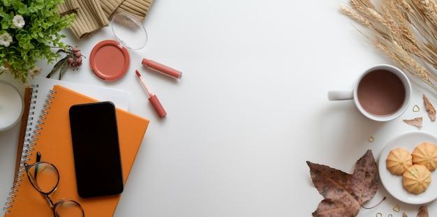 Obenliegender schuss des warmen beige weiblichen arbeitsplatzes mit laptop-computer, bilden und bürozubehöre