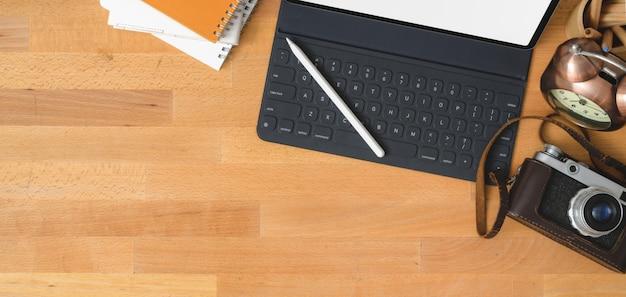 Obenliegender schuss des zeitgenössischen arbeitsplatzes mit digitaler tablette und kamera auf holztisch mit kopienraum