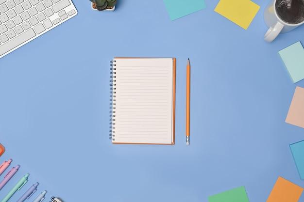 Obenliegender schuss von leerem notizbuch und bürobedarf auf blauem hintergrund.