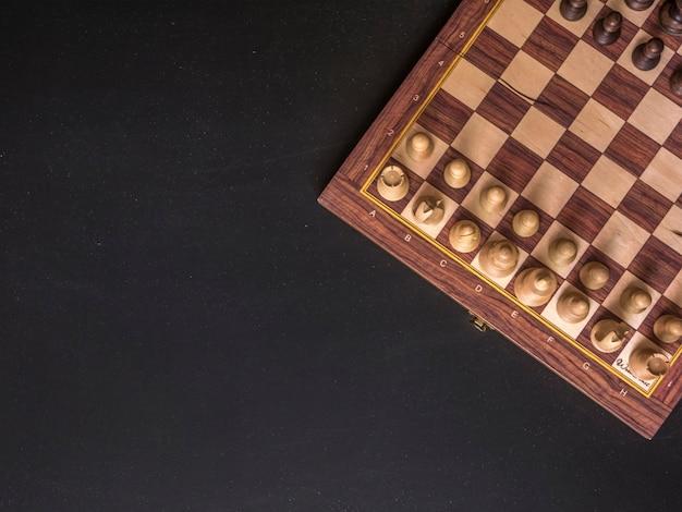 Obenliegendes kopienraum-schachbrett auf schwarzer dunkler tabelle
