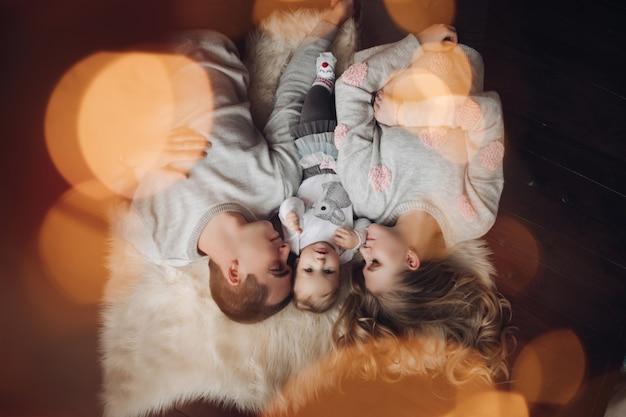 Obenliegendes porträt der schönen familie auf pelzteppich