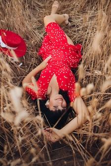 Obenliegendes stockfoto einer atemberaubenden jungen dunkelhaarigen frau im leuchtend roten tupfenkleid und in den fersen lächelnd in der kamera, während auf dem boden im weizenfeld entspannend.