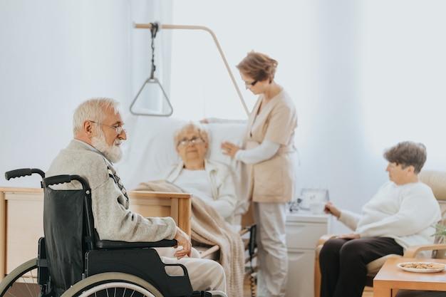 Oberarzt in beiger uniform spricht bei einem spaziergang durch das krankenhaus mit einem älteren patienten