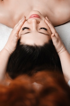 Obere ansicht der jungen schönen kaukasischen frau, die eine gesichtsmassage in einem spa-salon durch eine kosmetikerin vor gesichtsbehandlungen tut.