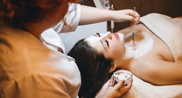 Obere ansicht einer charmanten frau mit dunklem haar, leanin mit geschlossenen augen, während eine weiße hautpflegemaske in einem kurort hat.