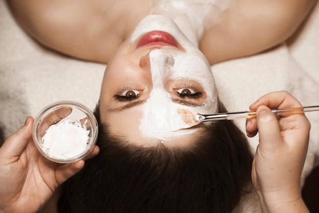 Obere ansicht einer reizenden erwachsenen frau, die eine weiße hautpflegemaske in einem spa-salon beim betrachten der kamera lächelt.