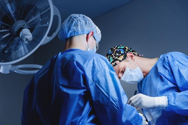 Obere blepharoplastik. chirurg führen plastische operationen durch. 2 chirurgen entfernen ein stück haut vom augenlid. transkonjunktivale blepharoplastik. operation.