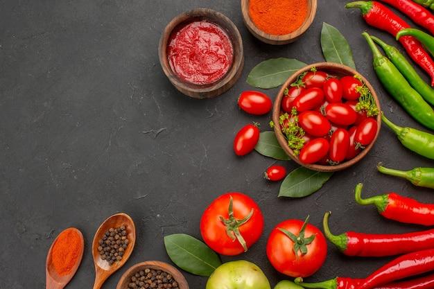 Obere hälfte ansicht einer schüssel kirschtomaten scharfe rote und grüne paprika lorbeerblätter gewürze in holzlöffel schalen ketchup heißen roten pfeffer pulver und schwarzen pfeffer und tomate auf dem boden
