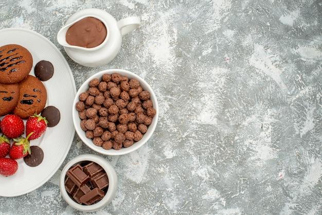 Obere hälfte ansicht schokoladenkekse erdbeeren und runde pralinen auf dem weißen ovalen teller und schalen mit pralinen müsli und kakao auf dem grau-weißen grund