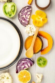 Obere hälfte ansicht weiße platte geschnittenes gemüse rotkohlkürbis blumenkohl gelbe paprika kurkuma in kleiner schüssel auf weißer holzoberfläche
