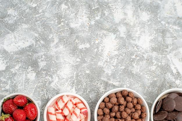 Obere halbansicht schalen mit erdbeerbonbons müsli pralinen am unteren rand des grauweißen bodens