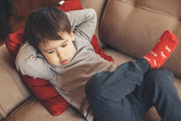 Obere seitenansicht eines kaukasischen jungen, der unten schaut und sich traurig fühlt, während er auf einem sofa mit einem roten kissen liegt