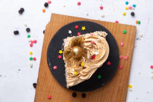 Oberes nahes ansicht köstliches kuchenstück innerhalb des dunklen tellers mit kerzen und kleinen sternzeichen auf dem weißen hintergrundkuchen süßer zucker backt tee