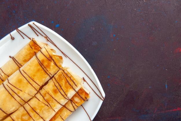 Oberes nahes ansicht köstliches süßes gebäck innerhalb platte auf dunklem raum