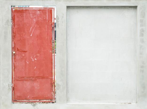 Oberfläche der schmutzigen roten stahltür mit zementwandbeschaffenheitshintergrund