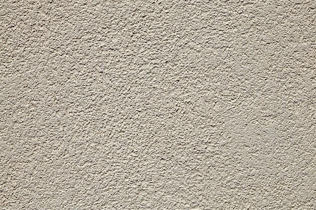Oberfläche der wand mit beige strukturiertem putz.