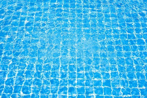 Oberfläche des blauen wassers im swimmingpool mit sonnenreflexion. welligkeit im pool.