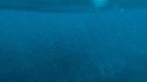 Oberflächenblau unter wasser mit plankton im tropischen meereshintergrund