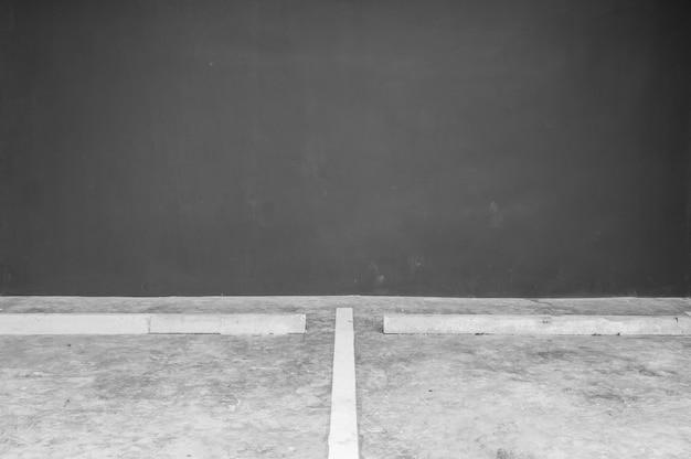 Oberflächenlinie schlitz der nahaufnahme für das parken auf zementboden mit unscharfer dunkelgrauer zementwand in der garage