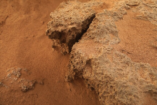 Oberflächensandgestein. felsiges ufer mit rotem sand des mittelmeers. selektiver fokus