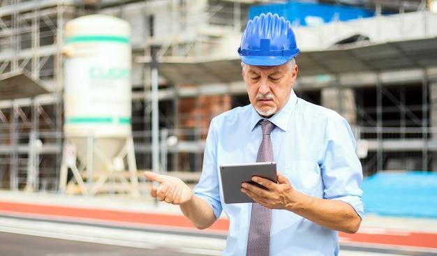 Oberingenieurmann im anzug und in sturzhelm, die an tabletten-pc in einem skeptikerausdruck arbeiten