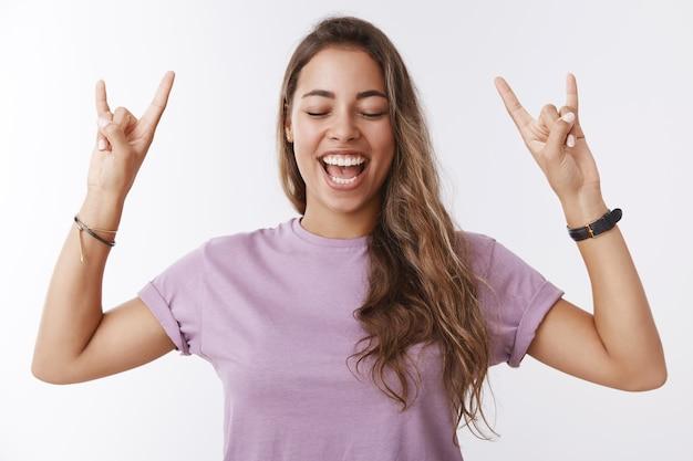 Oberkörper energetisiert sorglos attraktives junges tausendjähriges glückliches mädchen, das ein ticket gewinnt lieblingskonzert schreit ja geniale musik genießen, die rock-n-roll-geste zeigt, zunge kleben, augen schließen