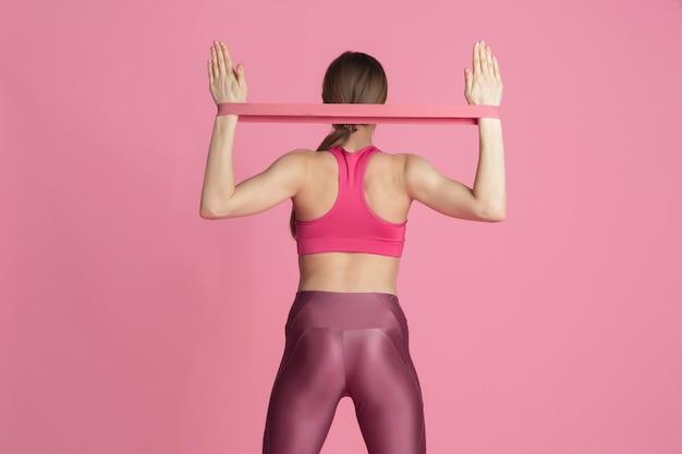 Oberkörper. schöne junge sportlerin, die im studio übt, einfarbiges rosa porträt.
