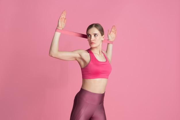 Oberkörper. schöne junge sportlerin üben, einfarbiges rosa porträt. kaukasisches modell mit sportlicher passform und gummizügen. bodybuilding, gesunder lebensstil, schönheits- und aktionskonzept.