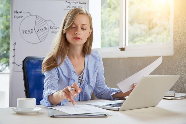 Oberkörperaufnahme der jungen blonden geschäftsfrau, die am schreibtisch arbeitet