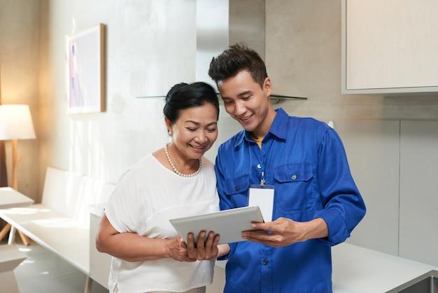 Oberkörperaufnahme des schlossers dem älteren kunden einen digitalen fragebogen zeigend