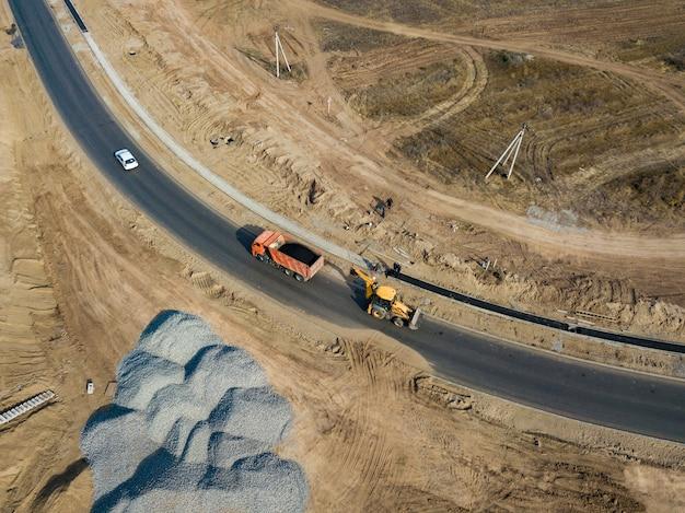 Oberste luftaufnahme des industriebaggers setzte asphalt in die kipperspur ein, um straße zu reparieren