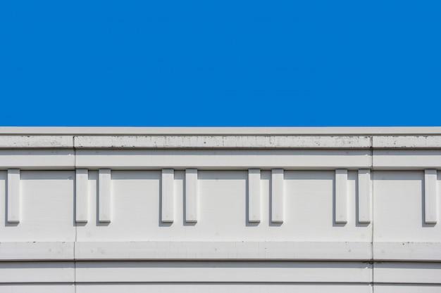 Oberteil des modernen designs der hohen gebäudewand mit klarem hintergrund des blauen himmels.