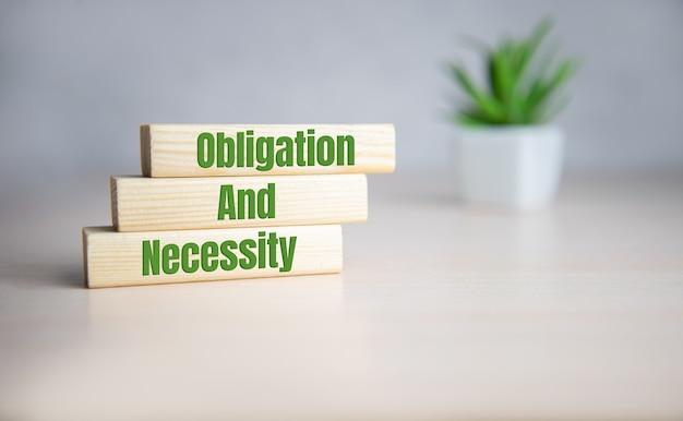 Obligation und notwendigkeit wort geschrieben auf holzklötzen