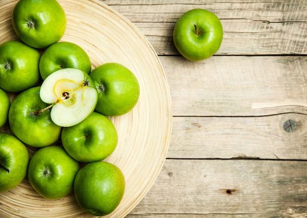 Obst. äpfel in einer schüssel auf hölzernem hintergrund