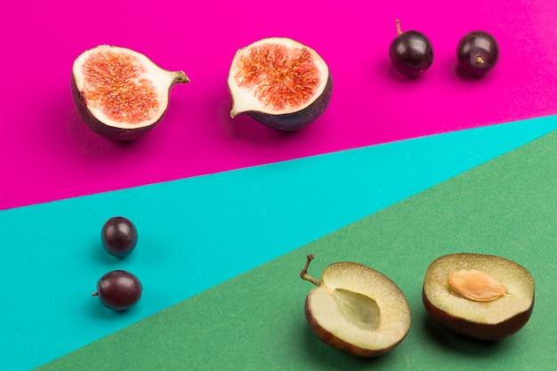 Obst auf farbigem papier. geometrische flache zusammensetzung von buntem papier und früchten: feigen, trauben, pflaumen. flach liegen.