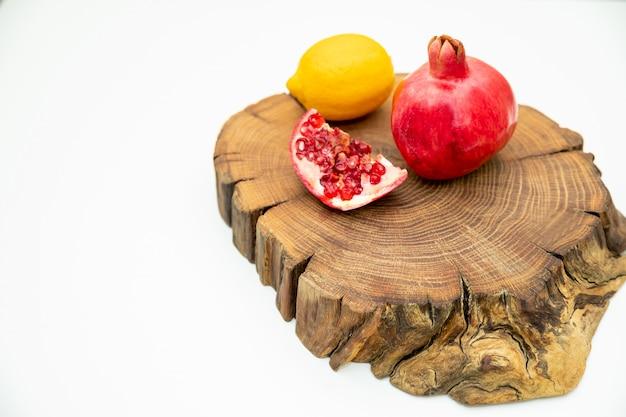 Obst besteht zur hälfte aus mandarine, zitrone. frisches obst auf holztisch, isolierte holzbrett. vitamin c aus früchten. gesundes essen, diät-konzept.