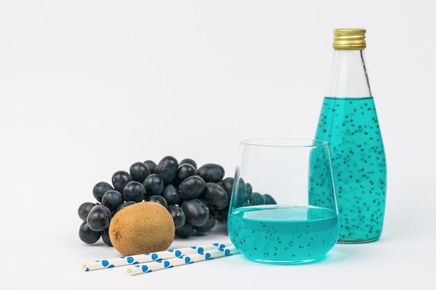 Obst, flasche und cocktailglas auf einer hellen oberfläche