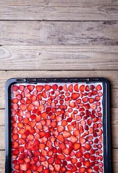 Obst. geschnittenes erdbeerbacken auf einer dunklen metallplatte im ofen. holztisch