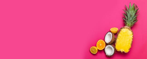 Obst hintergrund. ananas, kokosnüsse auf rosa hintergrund. sommerfrüchte. flache lage, draufsicht, kopienraum
