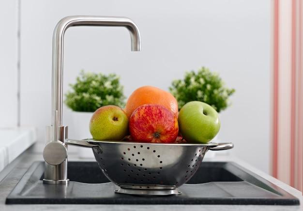 Obst in der tasse auf der küchenspüle in der nähe des wasserhahns.