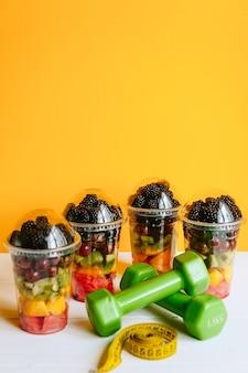 Obst in einem glas, eine hantel und ein maßband zum messen des körpers. konzept der gesunden ernährung und gewichtsverlust