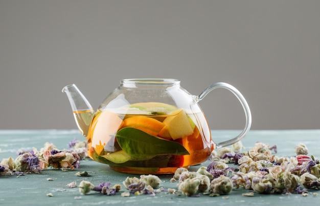 Obst infundiertes wasser in einer teekanne mit getrockneten blumen seitenansicht auf gips und grauer oberfläche