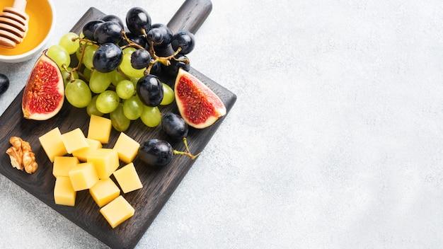 Obst, käse und nüsse auf einem schneidebrett
