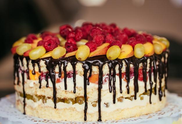 Obst, kuchen nackt. hausgemachter kuchen mit himbeeren, trauben und pfirsichscheiben.