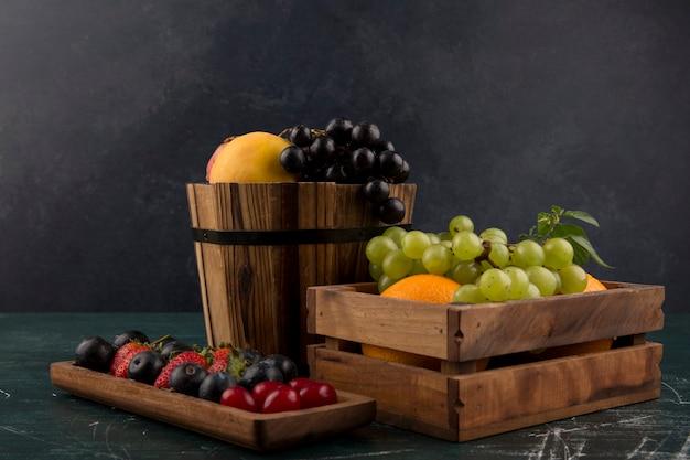 Obst und beeren mischen sich in holzbehältern