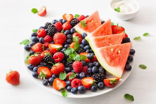 Obst- und beerenplatte mit joghurt über weiß. blaubeere, erdbeere, himbeere, brombeere, wassermelone
