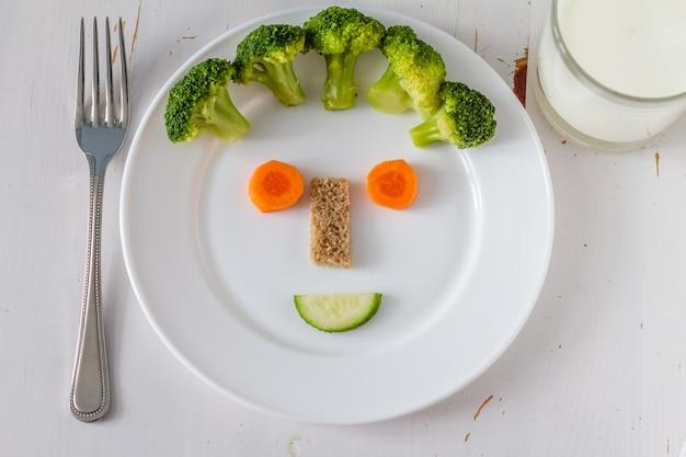 Obst und gemüse arrangiert, um kinder im lustigen gesicht anziehend zu schauen