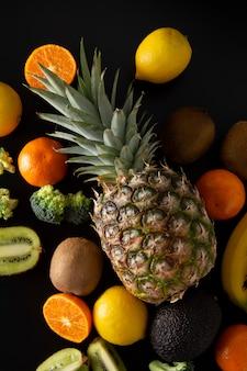 Obst und gemüse auf schwarzem hintergrund. gesundes essen, abwiegen.