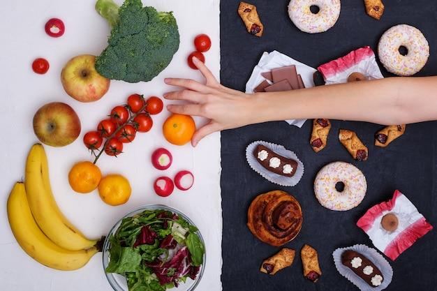 Obst und gemüse gegen donuts, süßigkeiten und burger