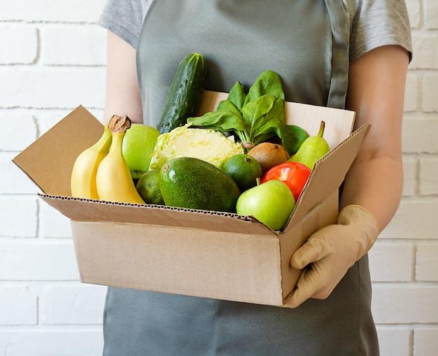 Obst und gemüse in einem karton in den händen des lieferers. lieferung von lebensmitteln aus dem laden nach hause.